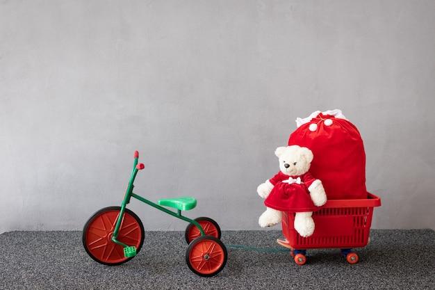 Teddybär trägt weihnachtskostüm, das auf vintage-dreirad sitzt. weihnachtsferienkonzept