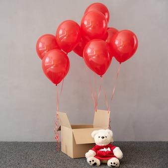 Teddybär trägt weihnachtskostüm in der nähe von box mit roten luftballons. weihnachtsferienkonzept
