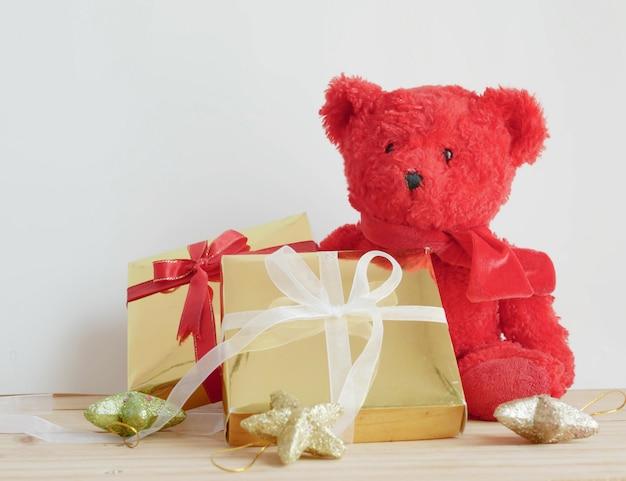 Teddybär und geschenkboxen mit sternen auf dem holzbrett