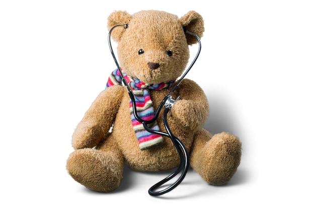 Teddybär und stethoskop isoliert auf weiß