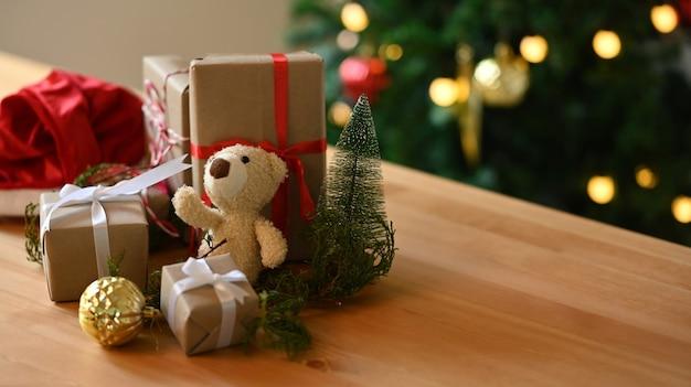 Teddybär und weihnachtsgeschenke auf holztisch im wohnzimmer.