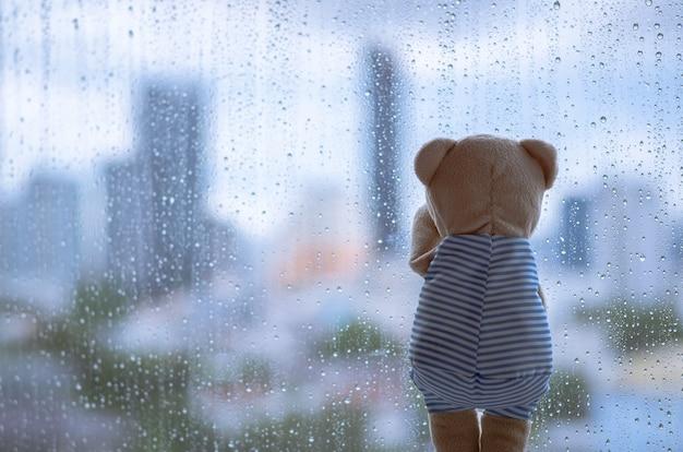 Teddybär weint allein am fenster, wenn es mit verschwommener stadt regnet