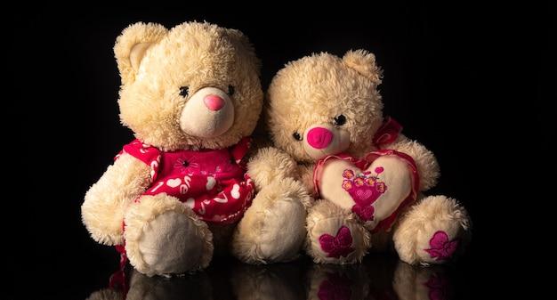 Teddybären halten sich gegenseitig, auf schwarzem hintergrund, selektiver fokus.