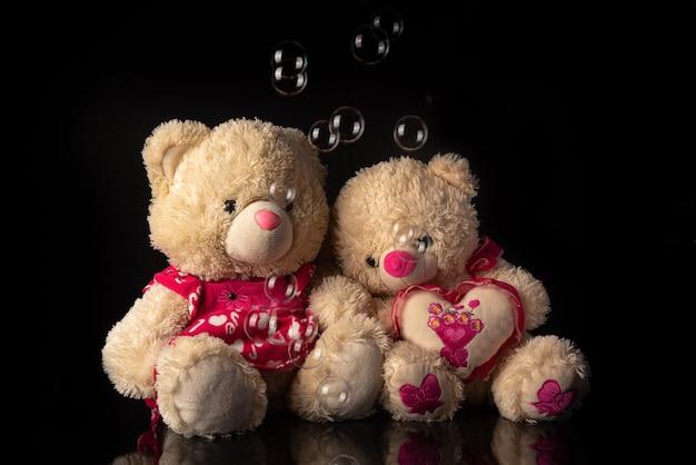 Teddybären mit seifenblasen auf schwarzem hintergrund, selektiver fokus.