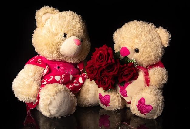 Teddybären mit strauß roter rosen auf schwarzem hintergrund, selektiver fokus.