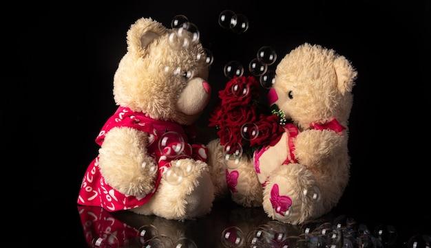 Teddybären mit strauß roter rosen, seifenblasen auf schwarzem hintergrund, selektiver fokus.