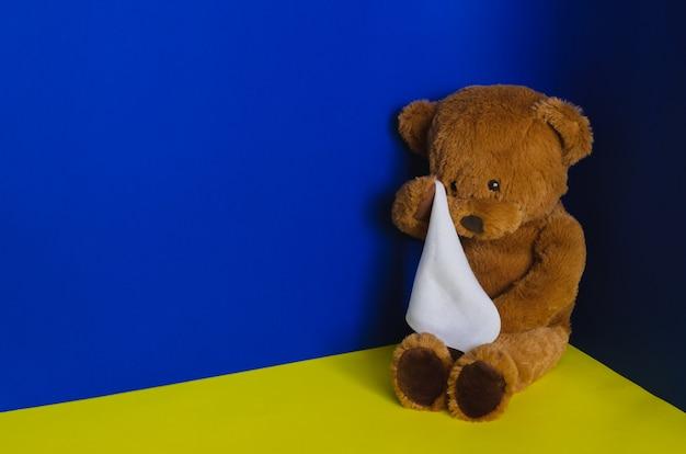 Teddybärpuppe sitzt an der ecke und weint mit taschentuch. kindesmissbrauchskonzept.