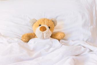 Teddybär, der auf dem Bett schläft.