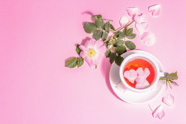 Tee aus hagebuttenblüten. sommervitamingetränk, hartes licht, dunkler schatten. rosa pastellhintergrund, ansicht von oben