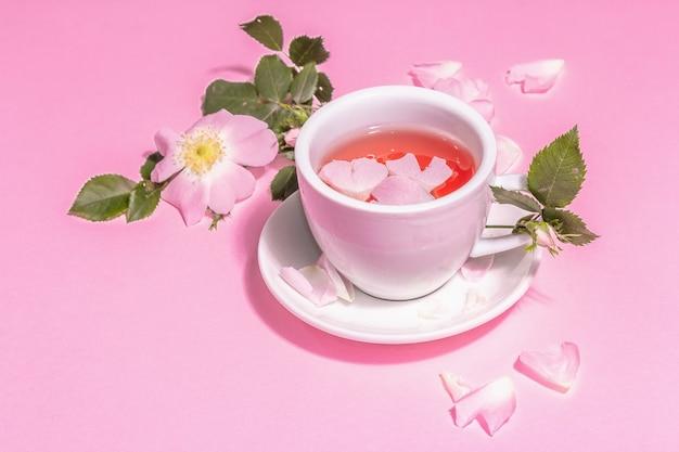 Tee aus hagebuttenblüten. sommervitamingetränk, hartes licht, dunkler schatten. rosa pastellhintergrund, textfreiraum