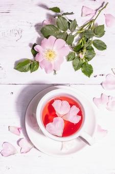 Tee aus hagebuttenblüten. sommervitamingetränk, hartes licht, dunkler schatten. weißer holzhintergrund, ansicht von oben