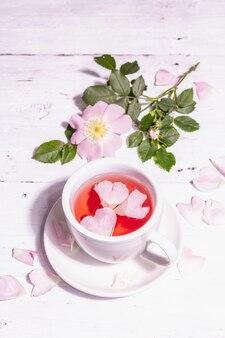Tee aus hagebuttenblüten. sommervitamingetränk, hartes licht, dunkler schatten. weißer holzhintergrund, textfreiraum