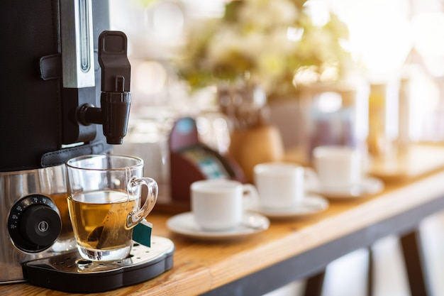 Tee aus kaffeemaschine und kaffeetasse auf dem esstisch dekoration
