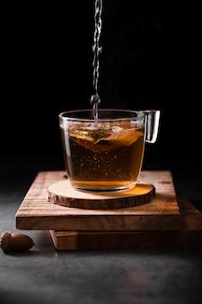 Tee, der in schalenatelieraufnahme gießt