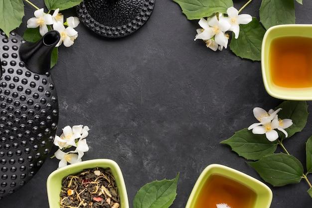 Tee der weißen blume und des trockenen krauts vereinbarte im rahmen auf schwarzem hintergrund
