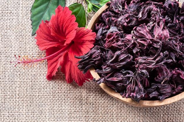 Tee des hibiscus (roselle, karkade) in der hölzernen schüssel auf leinwandhintergrund mit copyspace draufsicht.