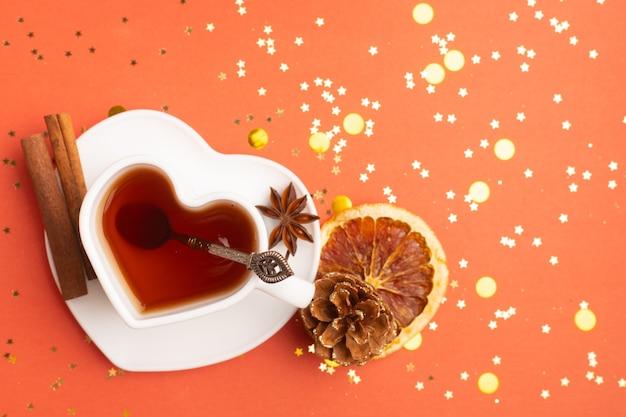 Tee des neuen jahres auf rotem grund . glitzer und roter hintergrund. urlaub. feiertagsdekorationen. heißer tee