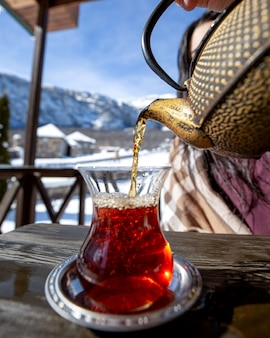 Tee eine frau, die schwarzen tee auf berghintergrund gießt