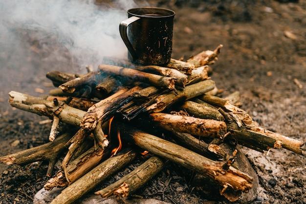 Tee im metallbecher erhitzt sich am lagerfeuer