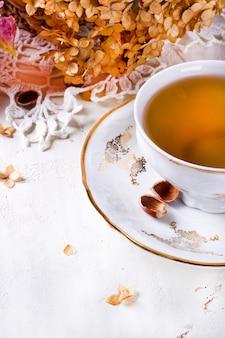 Tee im rustikalen vintage chic stil. garten-tee-party. teekanne mit trockenblumen. tasse tee mit herbstdekor auf dem tisch, mit hortensie und kürbis