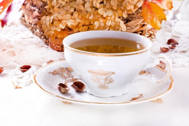 Tee im rustikalen vintage chic stil. gartentee-party. teekanne mit trockenen blumen.