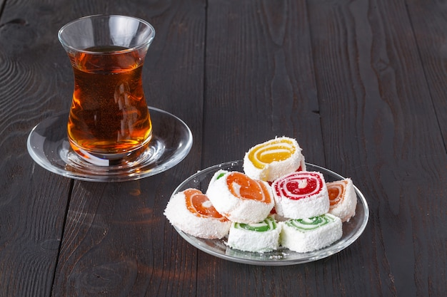 Tee im traditionellen armudu-glas mit süßigkeiten