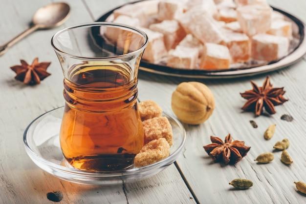 Tee in arabischem glas mit türkischem genuss rahat lokum und verschiedenen gewürzen über holzoberfläche