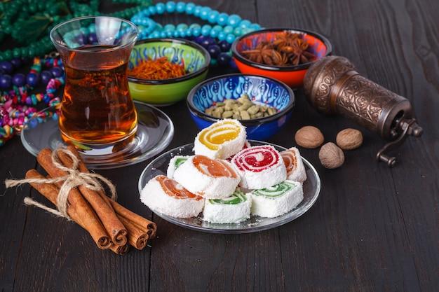 Tee in aserbaidschanischem traditionellem armudu und stapel von süßigkeiten auf tisch