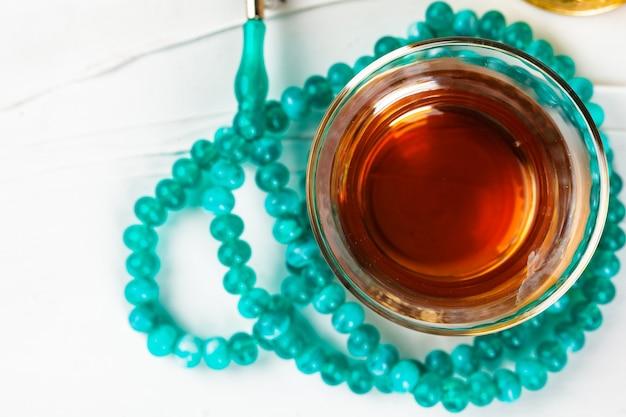 Tee in der glasschale und beten perlen auf weißem hintergrund