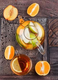 Tee in der tasse mit obst aufgegossenem wasser, draufsicht der früchte auf einer steinfliesenoberfläche