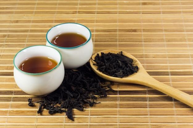 Tee in der tasse mit teeblatt