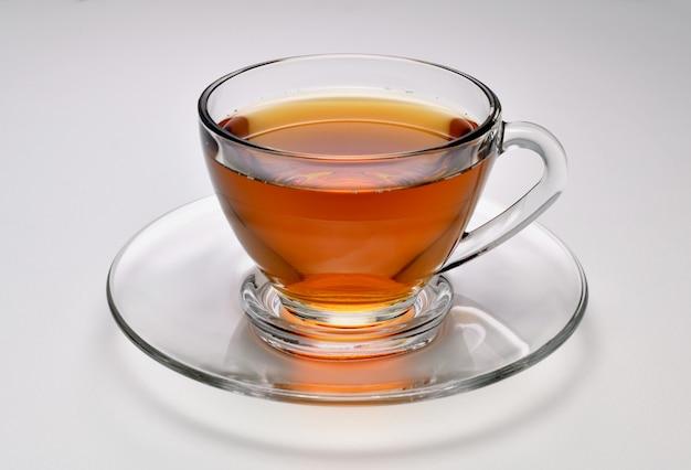 Tee in der transparenten glasschale auf weißem hintergrund