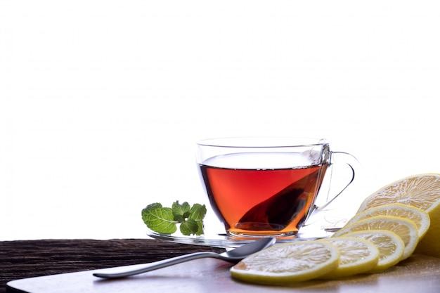 Tee in der transparenten glasschale mit zitrone auf weißem hintergrund