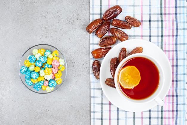 Tee in der weißen tasse mit datteln und einer schüssel süßigkeiten auf marmorhintergrund. hochwertiges foto