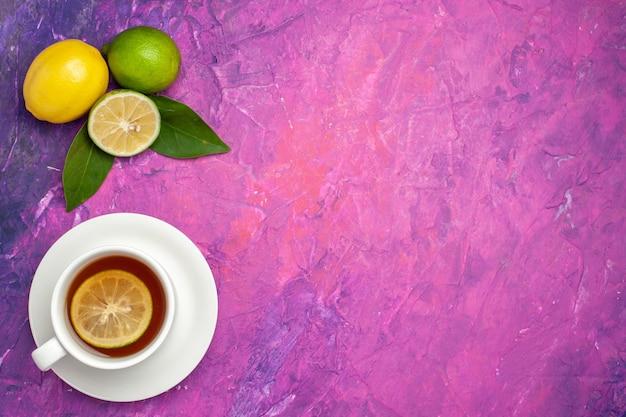 Tee in der weißen tasse weiße tasse tee mit zitrone auf der untertasse neben den zitrusfrüchten auf dem lila-rosa hintergrund