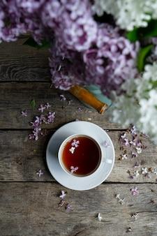 Tee in der weißen teetasse, blumenstrauß der lila blumen auf altem holztisch