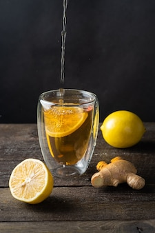 Tee in ein glas gegossen, eine zitrone, ingwer derevyannogm oberfläche.