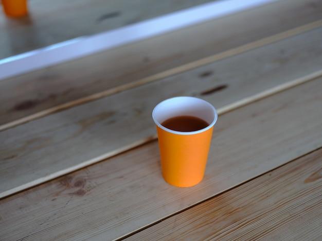 Tee in einem pappbecher auf dem tisch