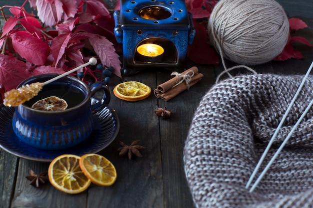 Tee in einer blauen tasse mit zitronenscheibe, braunem zucker, einer kerze in einem leuchter