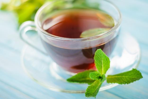 Tee in einer glasschale und in frischen tadellosen blättern