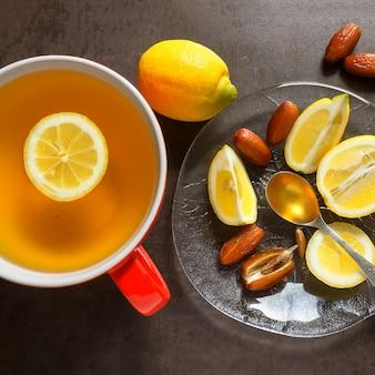 Tee in einer roten tasse. scheiben saftige zitrone, datteln und löffel honig.