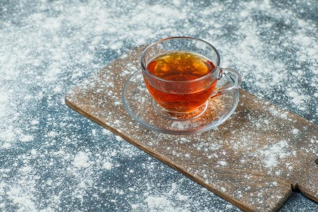 Tee in einer tasse mit gestreutem mehl high angle view auf beton und schneidebrett