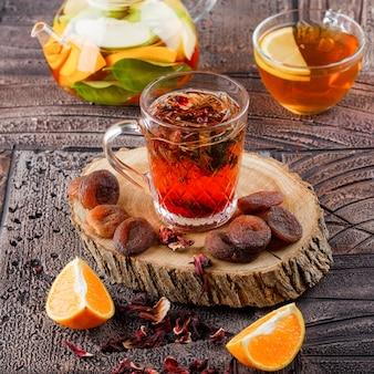 Tee in einer tasse mit getrockneten früchten, kräutern, wasser mit früchten, orange und holz