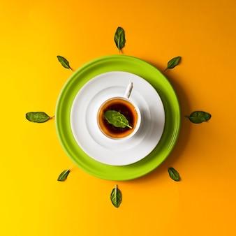 Tee in einer tasse mit grünen blättern auf orange wand. zeitkonzept.