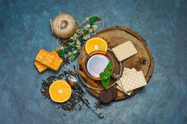 Tee in einer tasse mit kräutern, orange, gewürzen, keksen, faden, sieb draufsicht auf holzbrett und stuckhintergrund