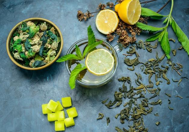 Tee in einer tasse mit zitrone, minze, getrockneten kräutern, zuckerwürfeln flach auf einer blauen oberfläche liegen