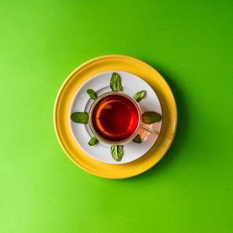 Tee in glasschale mit blättern auf grüner wand. zeitkonzept.
