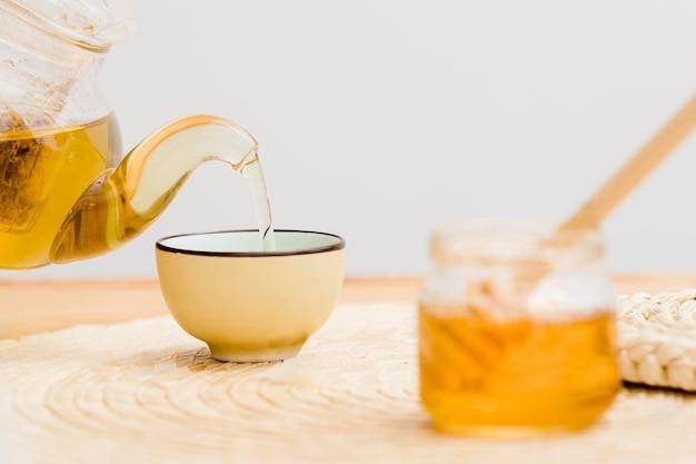 Tee in tasse aus teekanne gegossen