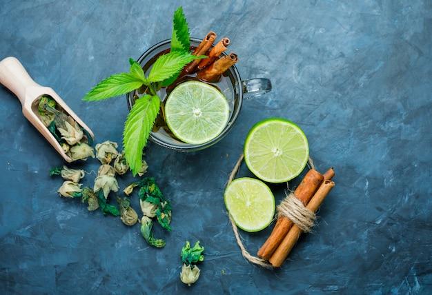 Tee in tasse mit minze, zimt, getrockneten kräutern, limette auf grungy blauer oberfläche, draufsicht.