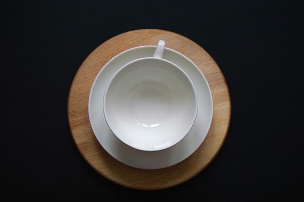 Tee in weißer tasse mit untertasse auf einem holzständer auf dunklem hintergrund